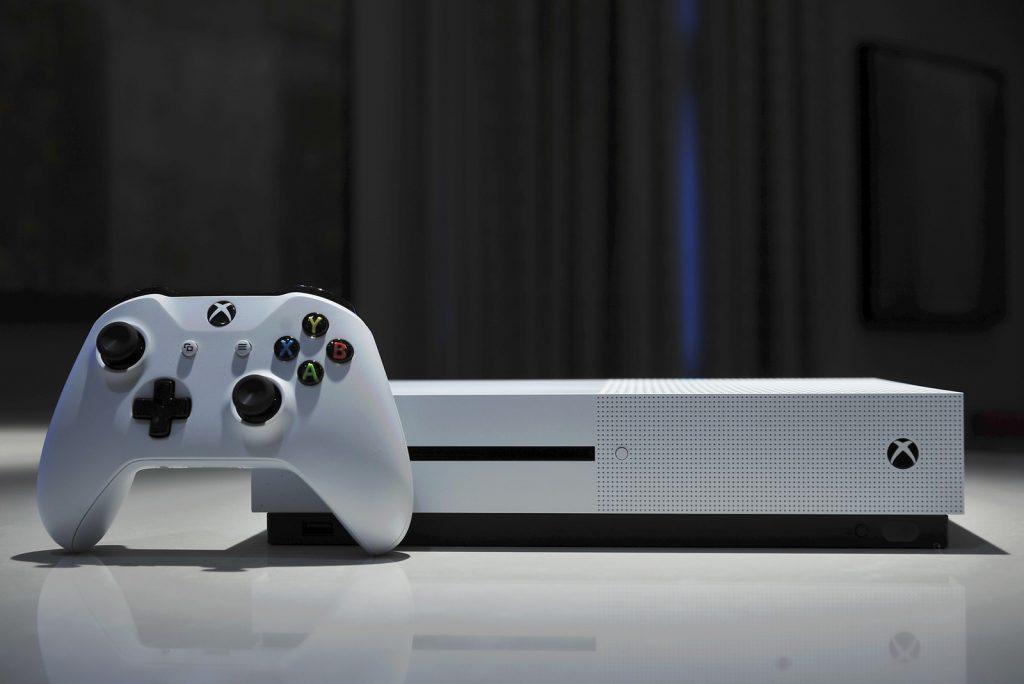 Consola Xbox en color blanco, con control individual sobre una mesa