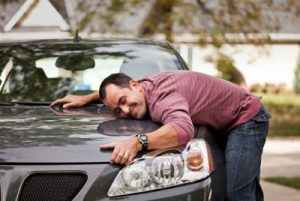 Hombre abraza auto usado