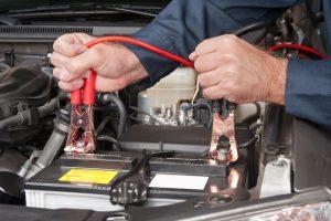 hombre arreglando bateria del coche