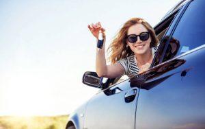 mujer feliz con su coche nuevo